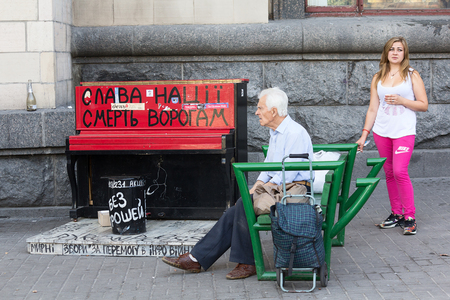 nationalist: Kiev, Ukraine - September 11, 2015: Citizens at the Independence Square near piano painted in the colors of the nationalist movement and the slogan Glory to the nation, the death of the enemy Editorial