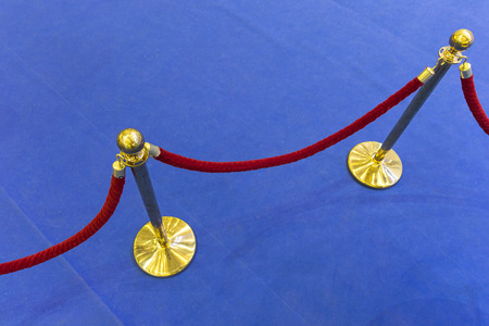 velvet rope: Red velvet rope and a blue carpet. Abstract background Stock Photo
