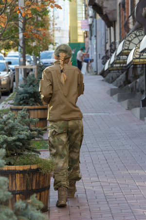 uniform green shoe: Girl dressed in military style on a city street. People