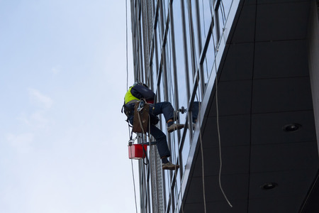 Industrial climber washes the facade of a multistory building. Industry Foto de archivo