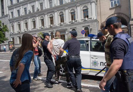 detain: Kiev, Ukraine - June 12, 2016: Police officers detain participants of the youth of the radical groups tried to prevent the holding of a gay parade