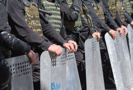 unrest: Police stand in cordon in the armor and shields Stock Photo