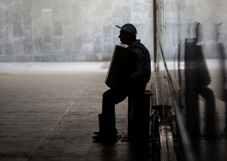 Silhouette of musician with accordion in underpass