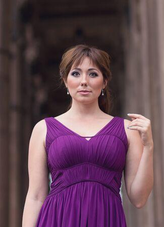 purple dress: Beautiful woman in purple dress near the column. People