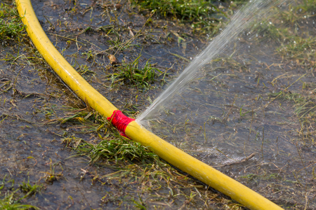 Water hose has sprung a leak when watering Stock Photo