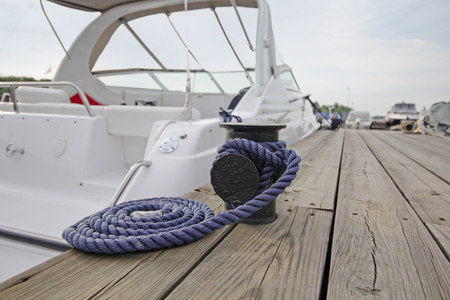 cleat: Mooring rope with a knotted end tied around a cleat on a wooden pier Stock Photo