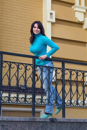 Hermosa chica en un jersey de cuello azul cerca de la barandilla. Gente