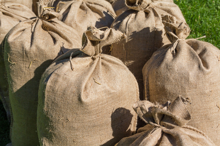 fastened: Pile of filled bags standing on the grass. Agriculture