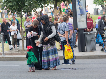 Kiev, Ukraine - June 19, 2016: Arab women with children close to issuing food item to the poor at the Independence Square