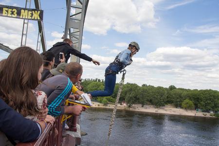 bungee jumping: Kiev, Ucrania - 12 de junio 2016: La muchacha intenta a sí mismo en el deporte extremo de saltar en marcha con un puente sobre el río