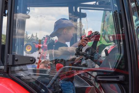 agro: Kiev, Ukraine - Ukraine, Kiev - June 10, 2016: Boy in the cab of the tractor on display exhibits International agro-industrial exhibition AGRO 2016 Editorial