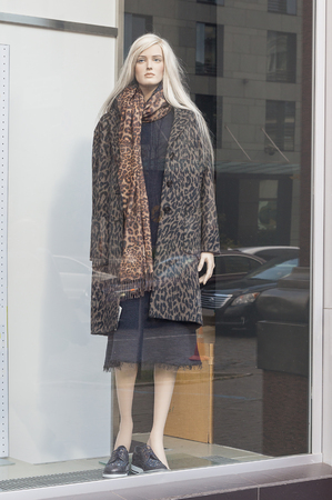 Female mannequin in a shop window. Fashion and sale