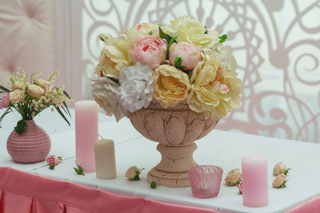 room decoration: Roses in a vase and candles on the table. Wedding decorations