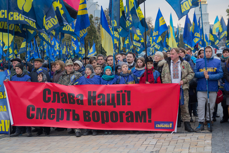 adherents: Kiev, Ukraine - October 14, 2016: Adherents of the Nationalist Party Svoboda during nastviyaav honor of Defender of the Fatherland. On transporant slogan Glory to the nation! Death to the enemies in the Ukrainian language Editorial