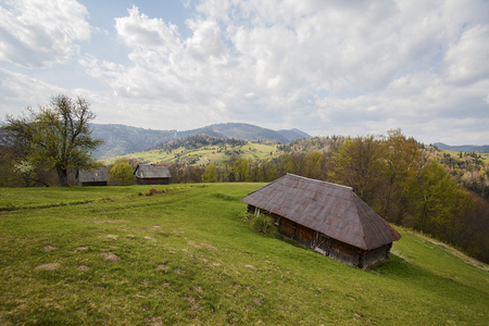 Old lodge on a green meadow on a background of mountains. Carpathians 版權商用圖片