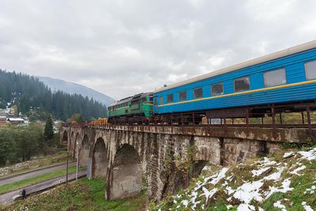 Diesel train traveling on the viaduct. Vorokhta, Ukraine Stock Photo