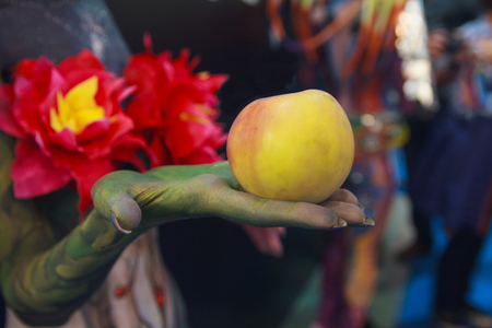 Forbidden fruit in the hand of the devil. Allegory Stock Photo