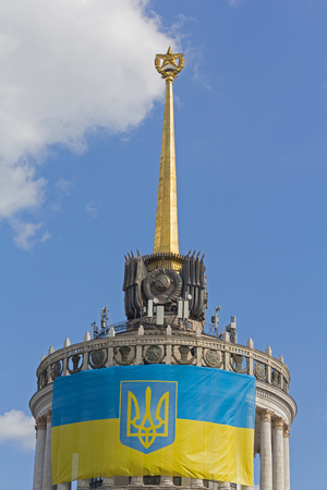 Ukrainian flag on the front of the building with the star, which was built in the times of the USSR. Kiev, Ukraine