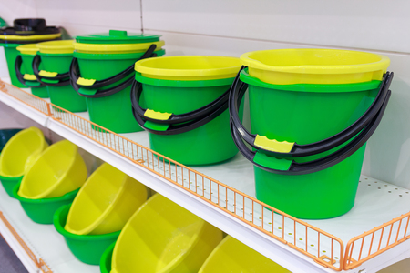Bright plastic buckets and bowls on the counter. Sale Stock Photo