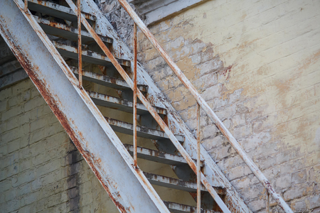 emergency stair: Rusty staircase at an old wall. Architectural abstraction