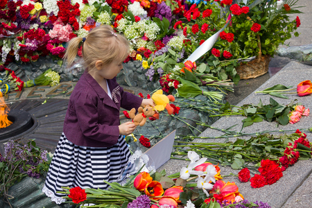 Kiev, Ukraine - May 9, 2015: Girl holds a toy at the monument to fallen soldiers of World War II