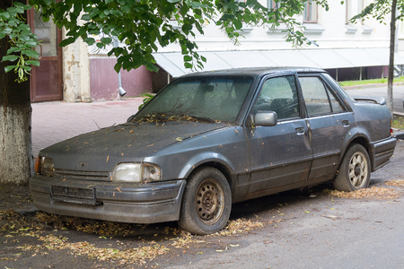 dirty car: Rusty abandoned car on a city street