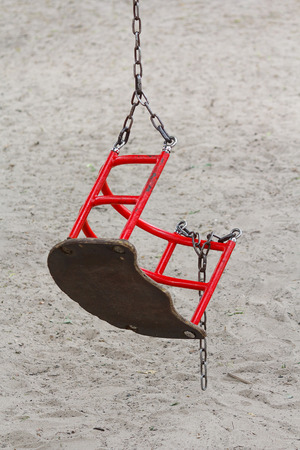 Broken swing hanging on the playground. Danger
