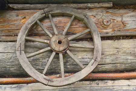 Wooden wheel from an ancient cart hanging on the wall of the hut Stock Photo