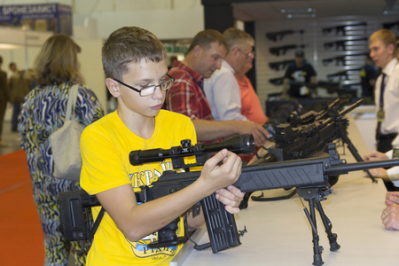 Kiev, Ukraine - September 22, 2015: Boy examines a battle rifle to a specialized exhibition Arms and Security - 2015 Editorial
