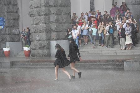 Kiew, Ukraine - 27. Mai 2016: Mädchen gehen ohne Regenschirm in den strömenden Regen entlang der Khreshchatyk Straße