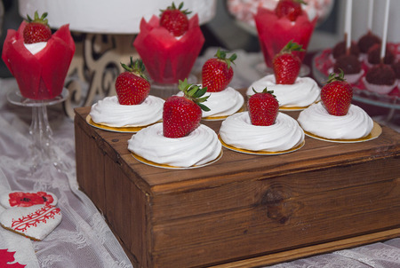 Cakes with strawberries and cream on the wedding table. Dessert