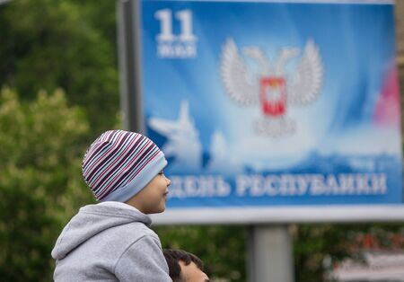 Donetsk, Ukraine -May 09, 2017: Boy on the shoulders of his father against the background of a banner calling for the celebration of the Republic Day