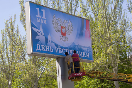 Donetsk, Ukraine - April 29, 2017: Workers glue Banner in the process of preparing for the celebration of the Day of Donetsk Peoples Republic, which will be held on May 11 Editorial