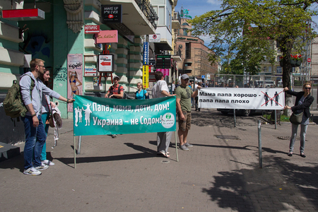 Kiev, Ukraine - June 12, 2016: Opponents of the parade of a sexual minority with a poster Dad, Mom, Children - Home! Ukraine is not Sodom! And Dad and Mom, its good, dad and dad are bad!  in Russian Sajtókép