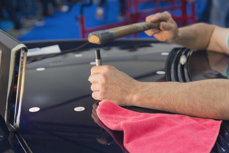 Hands of the master during the work on the straightening of the car's hood. Industry