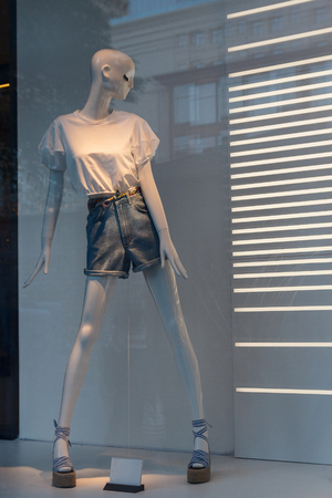 Female mannequin in a fashionable dress in a shop window