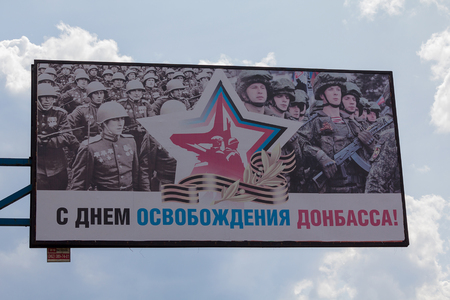 Makeevka, Ukraine - August 24, 2017: Banner on a city street depicting soldiers of the Red Army and fighters of the self-proclaimed Donets Peoples Republic with the inscription With the Liberation Day of Donbass in Russian Editorial