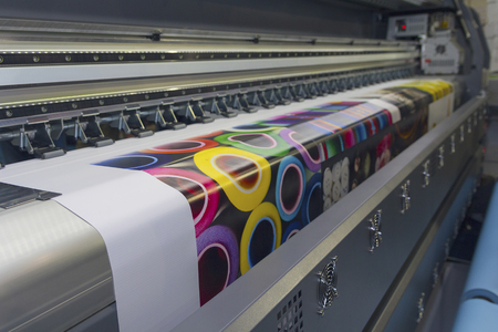 Large format printing machine in operation. Industry Imagens