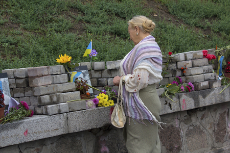 Kiev, Ukraine - August 24, 2016: Woman, flowers at the monument of the sky hundreds of dead during the 2014 revolution