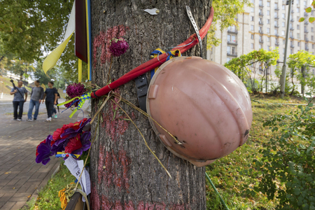Kiev, Ukraine - August 30, 2016: Helmet on a tree on an improvised monument to those who died during the revolution of 2014 Editorial