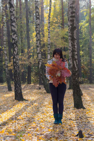 Girl throws leaves in autumn forest. People