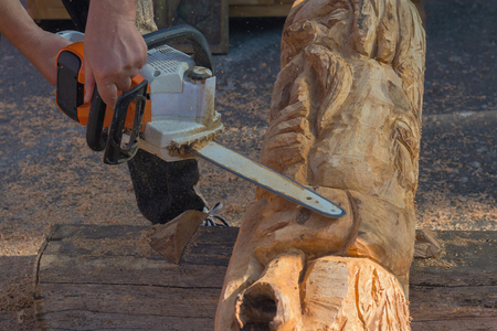 Masters hands with the saw plant sculpture from a tree. Art