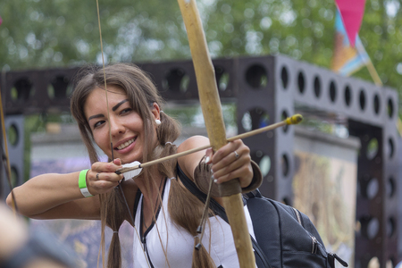 Kiev, Ukraine - August 06, 2017 - Girl aiming from an onion at the atrakration at the Vadalife Festival