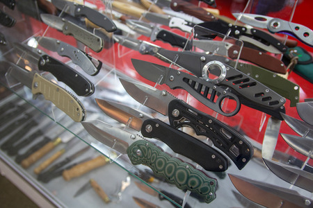 Variety of folding hunting knives on the counter