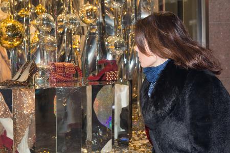 Woman looks in a show-window of shop. People Stock fotó