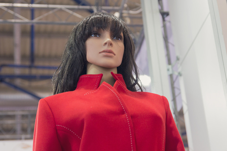 Realistic female mannequin in a red coat