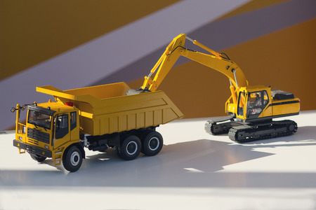 Model of a truck and an excavator on the stand. Industry