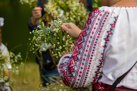 Woman in embroidery weaves a wreath of flowers on the traditional feast of Ivan Kupala. Ukraine
