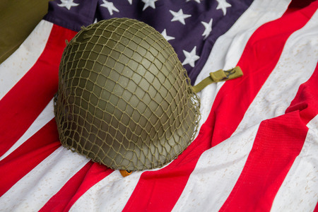 Soldiers helmet and the times of the Second World War and the US flag. Stock Photo