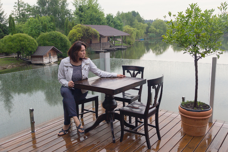 Woman at a cafe table by the pond. People Stock Photo